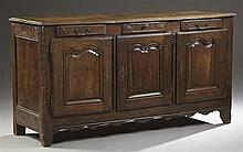 French Provincial Louis XV Style Carved Oak Sideboard, 19th c., the stepped edge curved corner top over three frieze drawers, above...