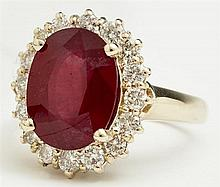 Lady's 14K Yellow Gold Dinner Ring, with an oval faceted 6.67 carat ruby, atop a border of round diamonds, total diamond wt.- .9 cts..