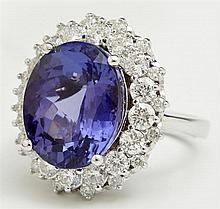 Lady's 14K White Gold Dinner Ring, with a 10.56 carat tanzanite atop a border of round diamonds above an outer border of round diamo..