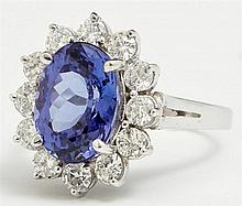 Lady's 14K White Gold Floriform Dinner Ring, with a central 5.07 carat tanzanite, atop a border of round diamonds, total diamond wt...