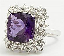 Lady's 14K White Gold Dinner Ring, with a 7.28 carat cushion cut amethyst, atop a pierced border of round diamonds, punctuated by ro..