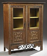 Spanish Style Carved Oak Bookcase, 19th c., the stepped edge top over double glazed doors with carved foliate fielded lower panels,...