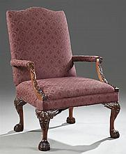 Large Georgian Style Carved Mahogany Upholstered Armchair, 20th c., with an arched back over upholstered arms on relief carved arch...