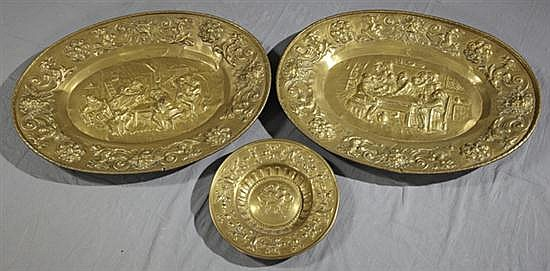 Group of Three Brass Repousse Plaques, late 19th c., two oval with central tavern scenes within repousse banding of winged gryphons....