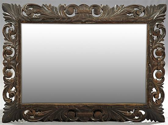 Jacobean Style Carved Beech Cushion Mirror, c. 1890, with a pierced leaf carved frame over a beveled plate, H.- 43 in., W.- 31 in., ...