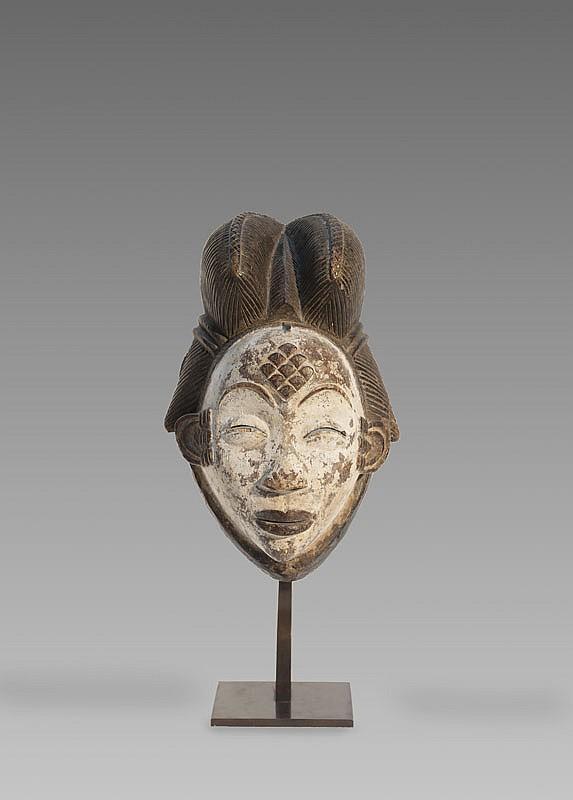 Masque de danse PUNU, Gabon. Belle coiffure élaborée, composée de trois coques d'où émergent deux tresses. Le visage à l'expression paisible et sereine, recouvert de kaolin. Bois léger, petits manques sur la coiffe et aux paupières. H.: 31 cm.