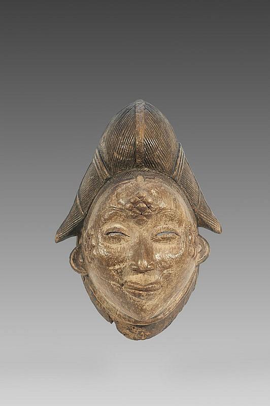 Masque de danse sur échasses «Okuyi»  PUNU, Gabon.  Coiffe à grande coque sagittale d'où émergent deux tresses.  Bois à patine brune, érodé par endroits, visage anciennement  recouvert de Kaolin. Ancienne restauration sur la collerette.  H. : 35 cm.
