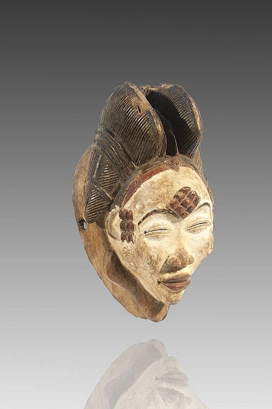 Masque de déambulation PUNU, Gabon. Très beau petit masque Ocuyi ou Mukuyi, le visage féminin aux yeux percés d'une fente placés sous de fins sourcils, la bouche aux lèvres délicatement sculptées, orné au front et aux tempes de neuf kéloïdes formant