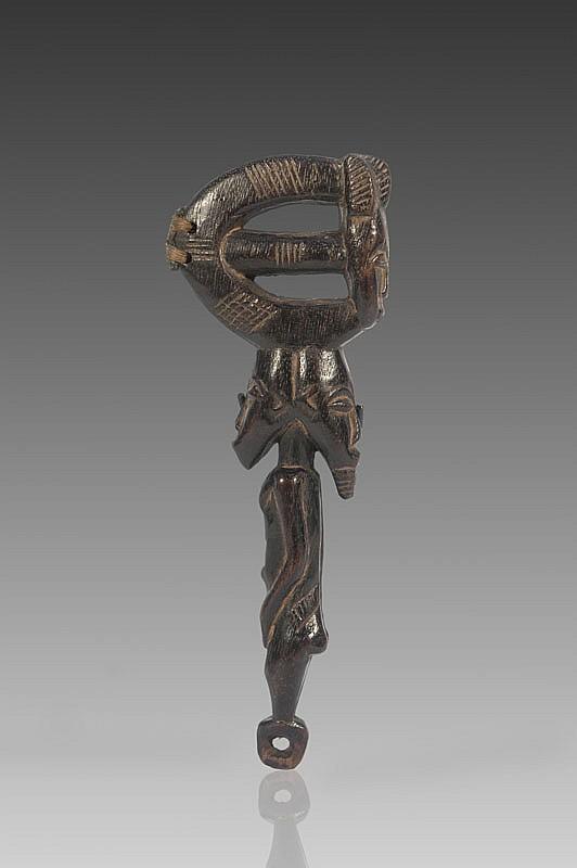 Marteau de gong BAOULÉ, Côte d'Ivoire. Intéressant instrument au manche surmonté d'une statuette à deux têtes dite janus. D'un côté le corps d'une femme, de l'autre la tête d'un homme barbu. Le percuteur figurant un masque Mblo à la coiffure