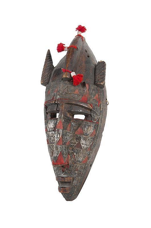 Masque Marka Région de Ségou, cercle de San, Bambara, Mali. Bois dur à patine brune, placage de laiton, brins de coton teints en rouge. H. : 25 cm. « Collecté à Bobo Dioulasso (Burkina Faso) ».