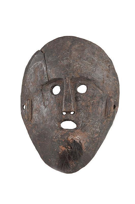 Masque de cérémonie shamanique Visage aux formes épurées, s'inscrivant dans un espace ovale. Bois dur, ancienne patine d'usage brune brillante par endroits. Népal. H. : 32 cm.