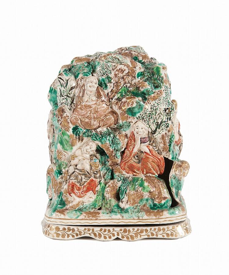 Boîte couverte en faïence  Japon, époque Meiji, fin du XIXème siècle ou début du XXème  siècle.  Le couvercle de la boîte ajouré et orné en relief de lohan assis dans  un paysage rocailleux planté de pins. H. : 20 cm.
