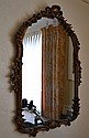 CARVED AND GILT MIRROR. Vertical format mirror with arched top form with floral band and shell decoration. No mark. Size; 38''H, 30W''. Condition: age appropriate wear.
