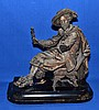 SPELTAR CAVALIER SCULPTURE ON WOODEN BASE   Speltar sculpture of seated cavalier set on ebonized wooden base.  13'' hieght.  6'' deep base.  12'' wide base.  No Mark.  Condition age appropriate wear.  Wear to metal finish. Scratches on wooden base.