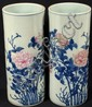 PAIR CHINESE CYLINDER VASES. Pair of newer Chinese cylinder vases with polychrome peonies and blue ringed top and bottom rim. Marked: Underglaze blue Chien Lung style seal mark. Size: 13 1/4''H, 5 1/2''Diam. Condition: one with spider crack on