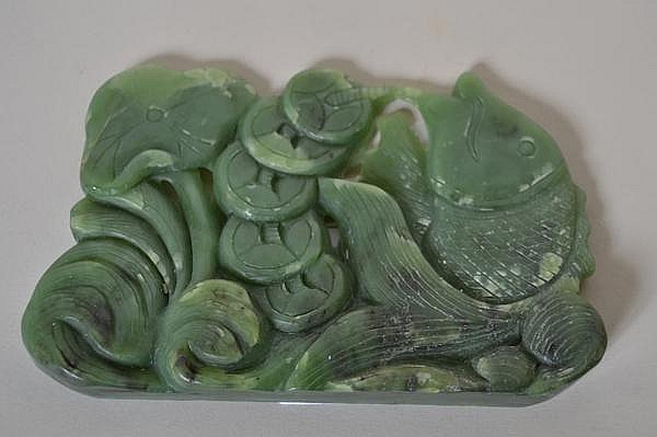CHINESE JADE CARVING OF CARP. Mottled green jade plaque of carp holding string of coins and lotus leaf. No mark. Size: 5 1/4''L,. 3 1/2''H, 3/4''Deep, deepest part. Condition: age appropriate wear.