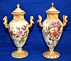 PAIR ROYAL RUDOLSTADT URNS  c.1882-1918 German Royal Rudolstadt Lidded Urns. Cream Ground with Polychrome and Raised Gilt Decoration.  11''H. 3 1/2''diam. Mark, Germany RW Rudolstadt. Condition, age appropriate wear. (wear to gilt)