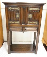 OAK CABINET WITH 2 DOORS OVER 2 DRAWERS. CARVED & PANELED. HAMMERED HINGES AND ESCUTCHEONS. 45 IN TALL. 29 IN WIDE.
