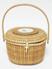 NANTUCKET BASKET WITH SWING HANDLE AND SCRIMSHAW TYPE DECORATED PANEL ON LID. 12 1/2 IN TALL. 9 1/2 WIDE X 7 IN DEEP.