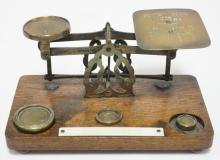 ANTIQUE *WINDLE & BLYTH* POSTAL SCALE. BRASS MOUNTED ON AN OAK BASE. 4 IN TALL 8 X 4 1/2 IN BASE.
