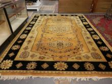 ORIENTAL RUG IN MUSTARD YELLOW, CREAM, AND BLACK. 13 FT 6 IN X 9 FT 7 IN. SOME WEAR.