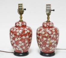 PAIR OF ORIENTAL PORCELAIN LAMPS IN RED WITH WHITE FLOWERS. 13 IN TALL. ONE IS REPAIRED.