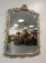 MIRROR WITH A SILVER GILT LEAF CARVED FRAME. 43 IN TALL BY 31 IN WIDE.