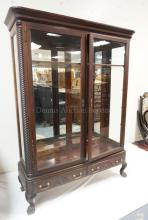 BOOKCASE WITH GLASS DOORS, ROPE CARVED COLUMNS AND PAW FEET. 49 1/2 IN WIDE. 67 IN TALL.