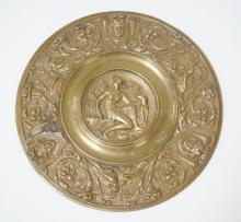 ORNATE BRONZE PLAQUE WITH A CLASSICAL WOMAN AND A DOG IN THE CENTER. THE OUTER RING HAVING BIRDS & CLASSICAL FACES. 6 7/8 IN DIA.