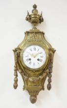 FRENCH BRONZE WALL CLOCK WITH A PORCELAIN FACE, BELLFLOWER DRAPING, AND FIGURED HEADS ON THE FINIAL. WORKS MARKED *J. MARTI*. 21 1/2 IN LONG.