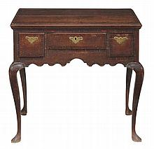 A George II oak lowboy, circa 1750, with a crossbanded and moulded...