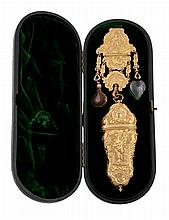 A George III gilt metal chatelaine, the scroll edged figural clip with two conforming panels beneath hung with an ogee sided necessaire worked in high relief with Hercules standing with his club, a lady with lute verso, each amidst scrolls on a