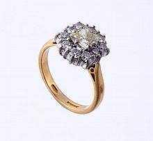 An 18 carat gold yellow diamond and diamond ring, London 2002, the central rectangular shaped yellow diamond, estimated to weigh 0.75 carats, in a claw setting within a brilliant cut diamond surround, approximately 0.30 carats total, maker's mark