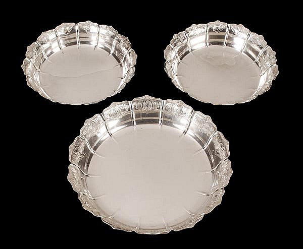 A matched suite of three silver scalloped dishes,