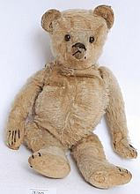 AN ANTIQUE c1900 believed Steiff teddy bear. Heavy pronounced snout, woodwool stuffing and original