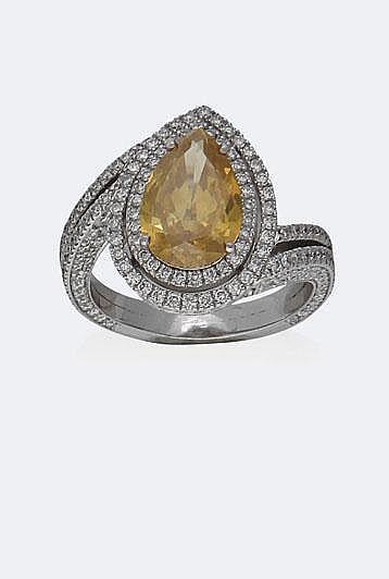 BAGUE en or gris, ornée d'un diamant taille poire, 2,83 carats certifié Fancy Yellow par le laboratoire GIA entouré de deux rangs de brillants fondant sur le corps asymétrique de la bague, total : 1,80 carat environ. Taille : 56 - Poids : 8,56 g brut