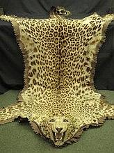 A LINED AND MOUNTED LEOPARD SKIN RUG, with full