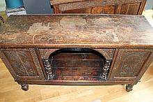 William and Mary oak dresser with two carved cupboards and central hutch with keystone arch.