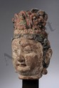 Tête du Boddhisattva Kwan Yin Avalokitésvara couronné d'un diadème incorporant l'image du Bouddha Amitabha, le visage serein marqué de l'urna au centre du front. Terre séchée polychromée. Chine. Dynastie Yuan. 1271 à 1368.