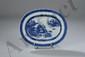 Plat ovale de la Compagnie des Indes en porcelaine blanche décoré en bleu cobalt sous couverte de pavillons au bord d'un lac. Chine. Dynastie Qing. Période Kangxi. 1662 à 1722. L20-26cm. Petites egrenures au marli.