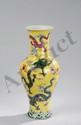Vase balustre à fond plat, base étroite, épaulement renflé et haut col évasé en porcelaine de la famille rose décoré en émaux polychrome sur couverte monochrome jaune de dragons rugissants autour de la perle d'éternité, flottants sur fond de nuages