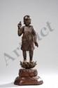 Figuration de l'enfant Buddha debout sur un lotus épanoui vêtu d'une robe monastique, les deux mains en mudras. Bronze à patine brune. Chine. Dynastie Ming. 1368 à 1644.  22cm+socle 6cm.