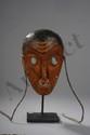 Masque de danse anthropomorphe au visage scarifié et  tatoué, les yeux ronds et le sourire ouvert sur une dentition. Bois polychrome. Chine. Yunan. Tribu Miao.
