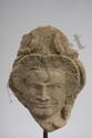 Tête de Devata provenant d'un haut relief de sanctuaire parée d'un lourd pendant d'oreille, la coiffure en éventail surmontée  de deux plumes. Pierre grès beige. Khmer. Cambodge. Angkor Vat. 13 ème siècle.  22cm.