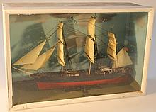 An mid-20th Century cased model of a frigate, painted in black and red with realistic sails, masting
