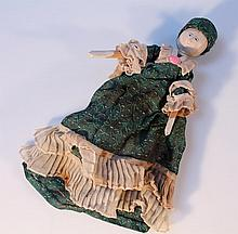 A 19th Century wooden pegged doll, with painted features and articulated wooden body in a green dres