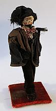 A Georgian wooden headed pegged doll, dressed as a sweep, with painted features, in velvet trousers,