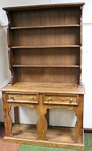 A 20th Century light elm dresser, the upper section with a fixed cornice, raised above Delft racks a