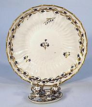 An early 19th Century Derby plate, of dished shaped circular form with a gilt outline and floral ban