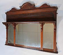 An Edwardian over mantel mirror, with a fixed carved cornice centred by a carved half sun motif, abo